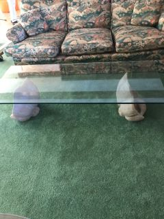 Glass top coffee table with shell base