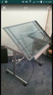 Metal framed glass top table on wheels