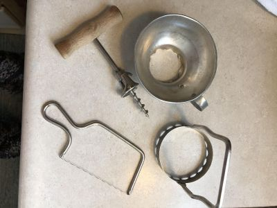 Four vintage kitchen utensils. Jar funnel, metal and wood in the corkscrew, cheese slicer, and food masher
