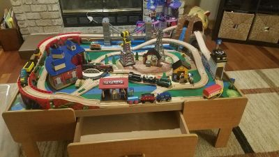 Imaginarium wooden train table and accessories. Pieces make sound and some trains motorized . 2 storage drawers.