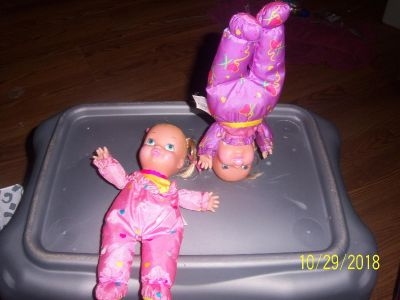 2 little dolls that have heavy heads that they can do headstands