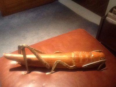 """Large hand carved grasshopper made in Spain with metal legs 23""""long."""
