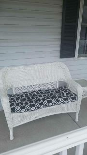 White wicker love seat with matching side table
