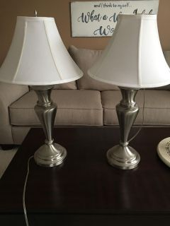 2 silver lamps with white shades