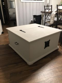 Coffee table chest that opens for storage.