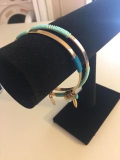 Set of two gold tone bangles one has small charms on it