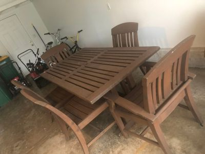 Wooden patio table and 5 chairs. Measures 70inches long and 30inches wise.