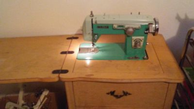 Vintage white sewing machine in cabinet