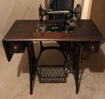 Antique sewing machine from the 1800s with wooden cover