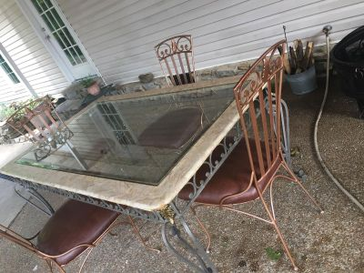 Decorative metal table with glass top and four metal chairs