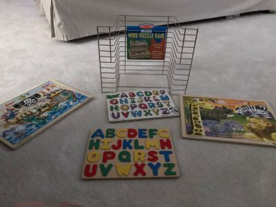 Melissa and Doug puzzle rack with 4 puzzles
