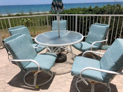 Glass top patio table and 5 rocker/swivel chairs.