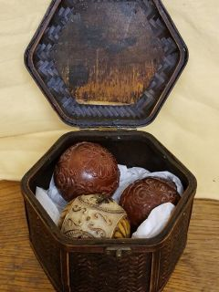 Set of three balls in a wooden storage container