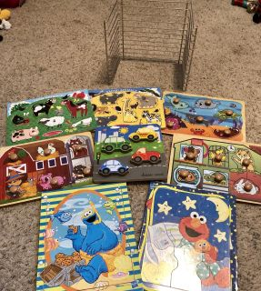 Six wooden puzzles, two extra cardboard puzzles, puzzle rack. Great condition