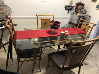 Nice glass top dining table with matching chairs. Has palm tree design on chairs.