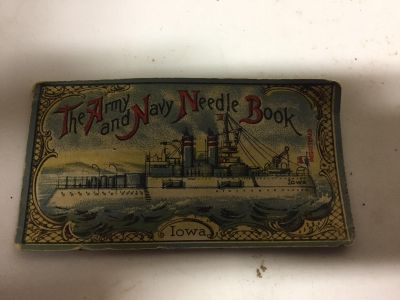 The Army and Navy Needle Book USS Iowa on the front and Eagle on the back. It has some meddles in it.