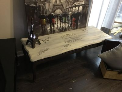 Antique coffee table refurbished in smooth whites and light grays accented by chic French boutiques signs and Paris places