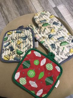 Three potholders, the white ones have stains, the Christmas one does not have any stains