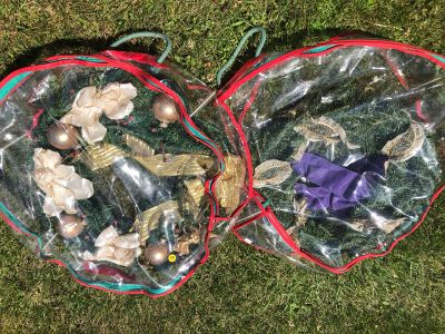 Two wreaths and plastic storage wreath holders