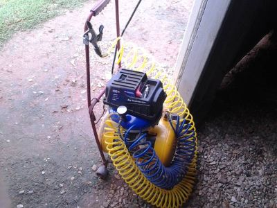 6 gallon air compressor with accessories on a dolly