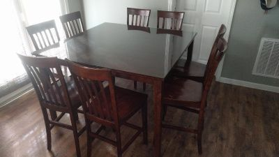 Solid wood bar-height dinner table with hidden leaf, glass top, eight chairs