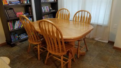 Round brown wooden pedestal table with four chairs