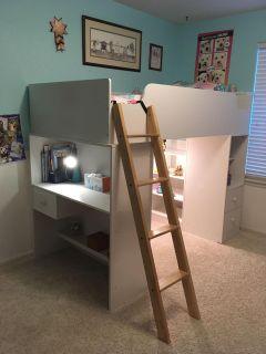 Lofted twin bed with desk and shelves.
