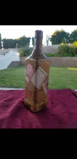 Repurposed liquor bottle in vintage stamp and mail