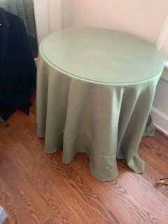 Round table with glass top and green tablecloth
