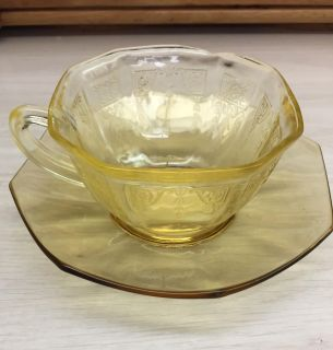 Pretty yellow cup and saucer. Maybe depression glass