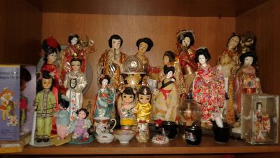 All sorts of oriental dolls figurines also hutch or cabinet includaedincluded cabinet glass doors