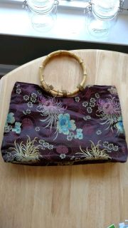 Beautiful handbag with Magnetic closure and wood handles made out of silky material in good condition