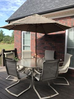 Heavy duty patio set. Set comes with umbrella, octagon table and 6 chairs. Two of the chairs need fabric repairs but are still usable.