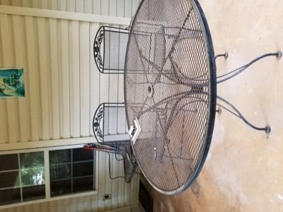 Black wrought iron patio set. 48 inch round table with 2 spring back chairs and 2 rocking chairs...