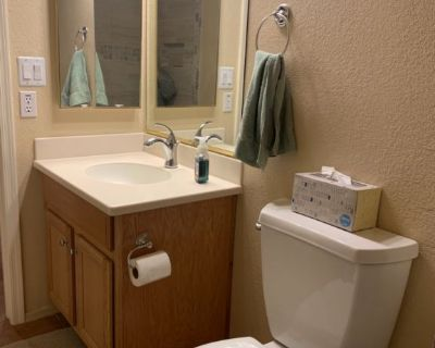Oak vanity, white toilet, medicine cabinet, and wall mirror.