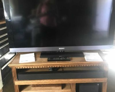 45 inch Sony Bravia TV with home theater system and oak cabinet