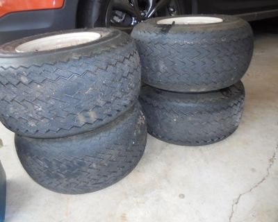 Four golf cart tires mounted to rims
