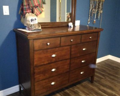 Queen bed with 2 drawera storage, 2 drawer nightstand, and 9 drawer dresser with mirror