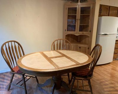 Oak table with ceramic tiles and corner hutch.