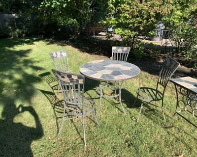 Slate-top wrought iron patio table with 4 chairs, side table, and wall sconce