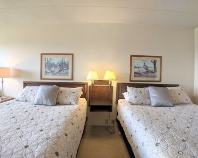 Cedar Lodge, Lake Winnipesaukee area. A beautiful room with Lake Winnipesaukee views, a small deck, mini fridge, microwave and coffee maker. 2 Queen beds and a full bathroom offer 2-4 people simple hotel style accommodations at the lodge. - Weirs Beach