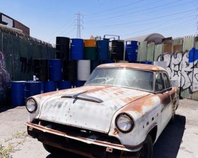 Industrial backdrop with barrels and classic car, Los Angeles, CA