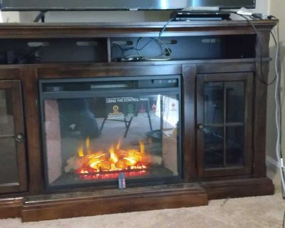 Tv stand table with traditional wood fire place with remote control and can heat up to a 1000 square feet area.