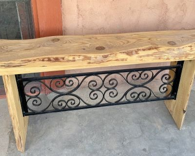 Handcrafted juniper bench with decorative wrought iron underneath,