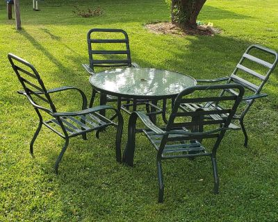 Outdoor patio set glass top table and 4 metal chairs.