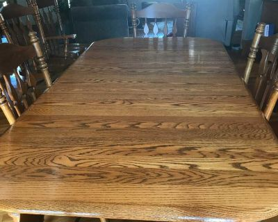 Solid oak dining table with four regular chairs and two captains chairs and matching China cabinet.
