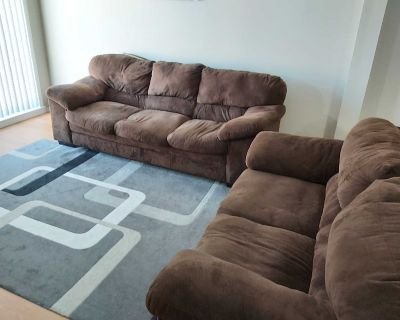 Dark brown fabric sofa and loveseat in good used condition.