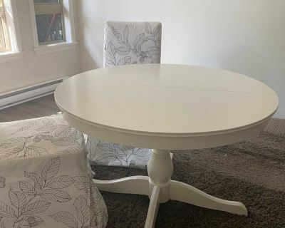 White circular dining table with three chairs